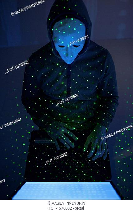 High angle view of green lights over computer hacker wearing mask using laptop