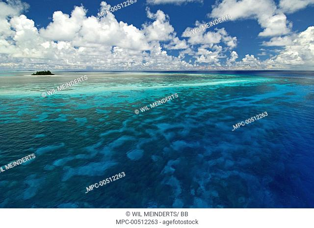 Clouds above sea and island with barrier reef, Bijoutier Island, Seychelles