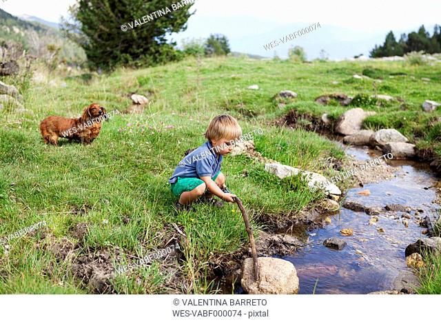 Spain, Cerdanya, little boy playing on a meadow at a brook