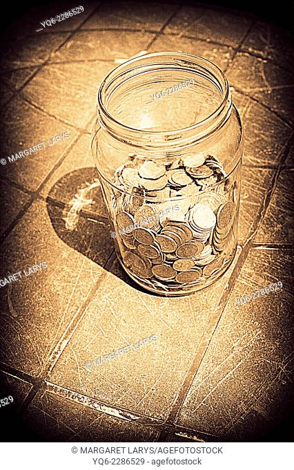 Old coins in the jar on the grungy background
