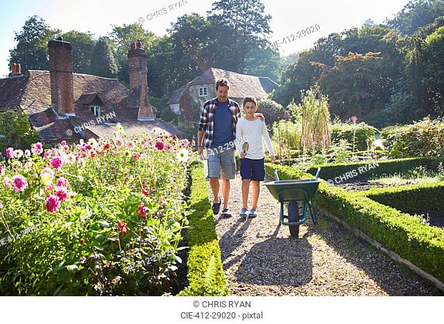 Father and son walking in sunny garden