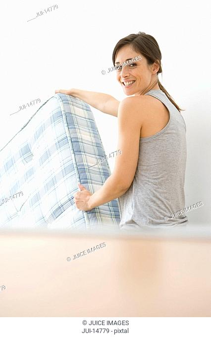 Woman moving mattress, smiling