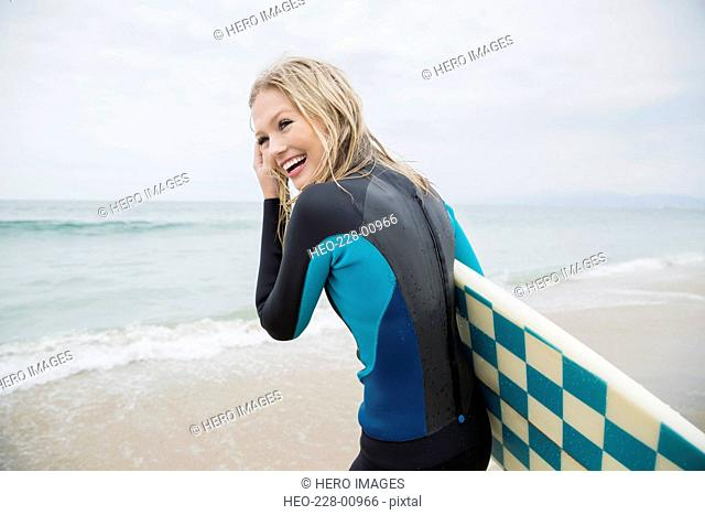 Smiling blonde female surfer with surfboard on beach