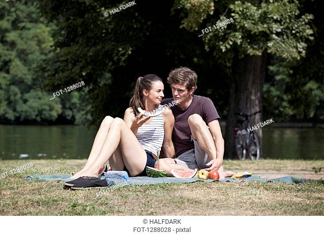 Young couple sitting on picnic blanket, holding water melon slice