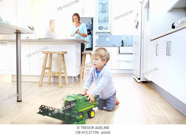 Women cooking in kitchen while boy plays with toy tractor on floor