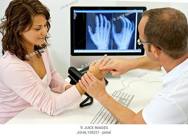 Doctor and patient looking at x-ray and hand in doctor's office