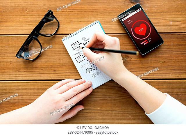 health care, planning and people concept - close up of woman or student drawing scheme in notepad with pencil and eyeglasses with heart rate on smartphone on...