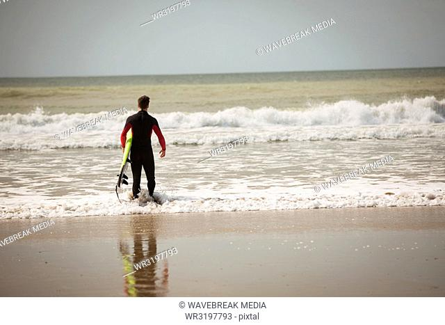 Surfer with surfboard looking at the sea from beach