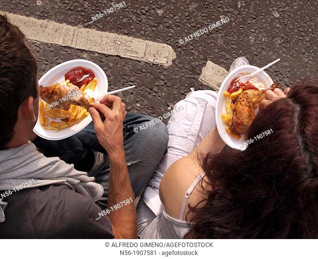 couple eating in the street, Notting Hill Carnival, London