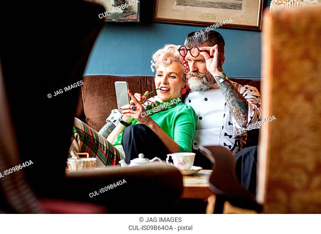 Quirky vintage couple looking at smartphone in tea room