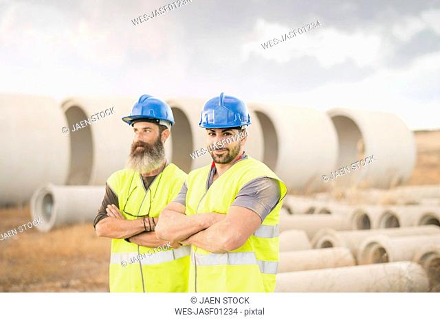 Two workers posing outdoors near to concrete pipes
