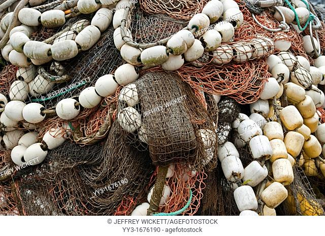 Colorful salmon seine commercial fishing nets stacked on shore in Sitka Alaska , USA