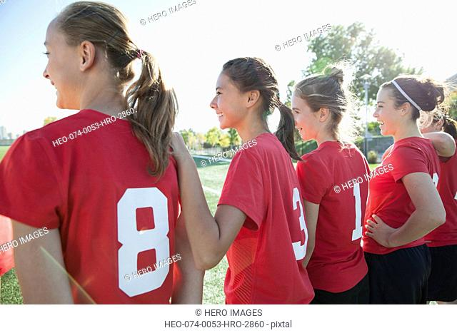 Soccer players watching soccer game from sideline