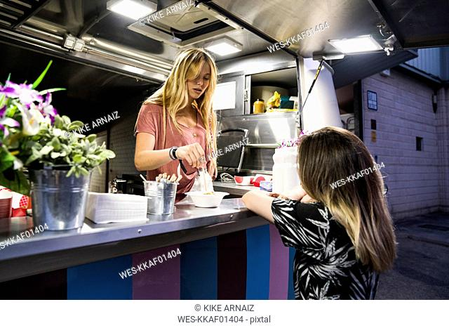 Young woman in a food truck serving customer