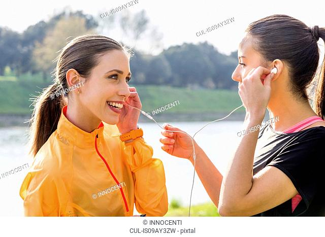 Two female friends outdoors, sharing earphones, listening to music