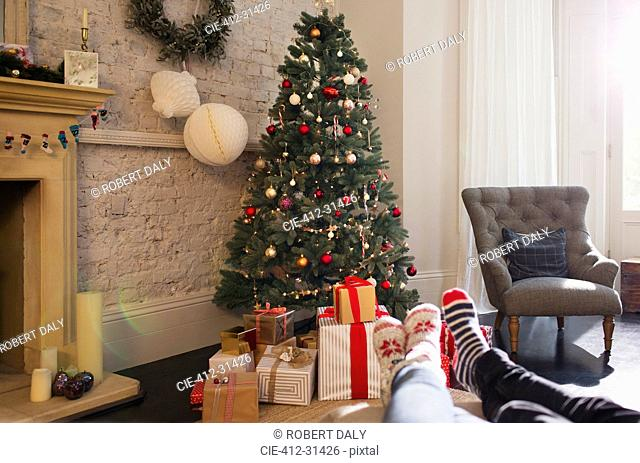 Relaxed couple wearing socks with feet up near Christmas tree in living room