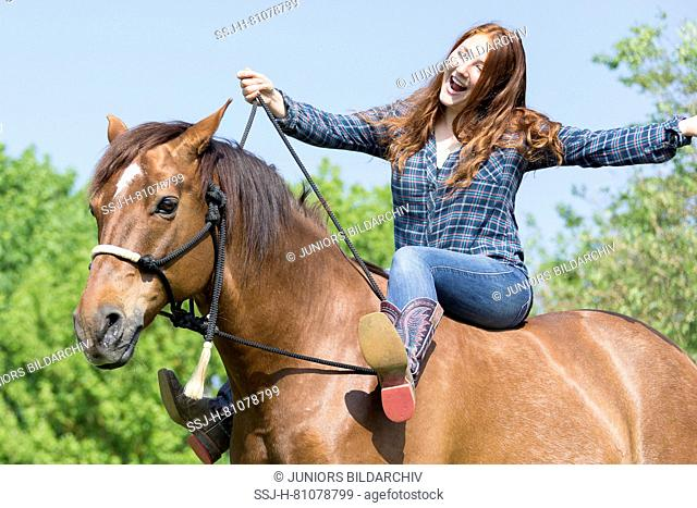 Missouri Fox Trotter. Red-haired young woman on chestnut gelding on a pasture, one boot on a rein. Switzerland