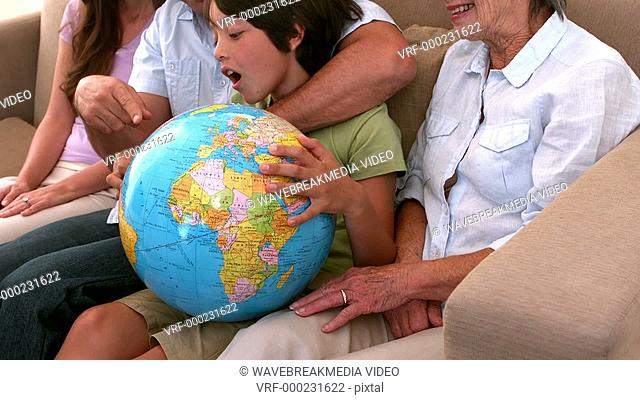 Extended family looking at globe together on couch in slow motion