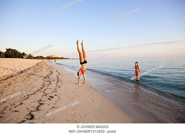 Girl doing handstand on beach