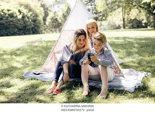 Two young women and a boy looking at cell phone next to teepee in a park