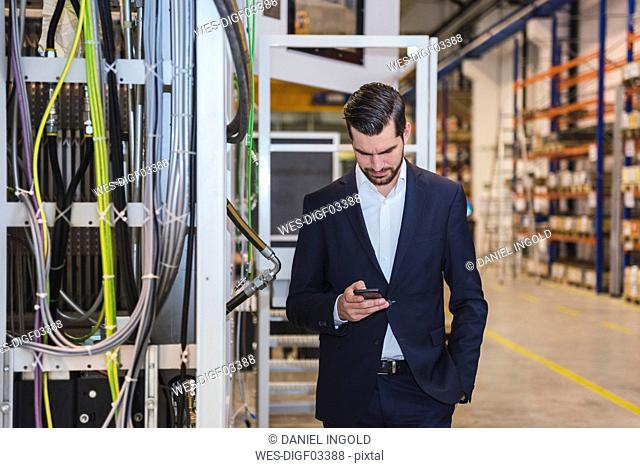Businessman in factory checking cell phone