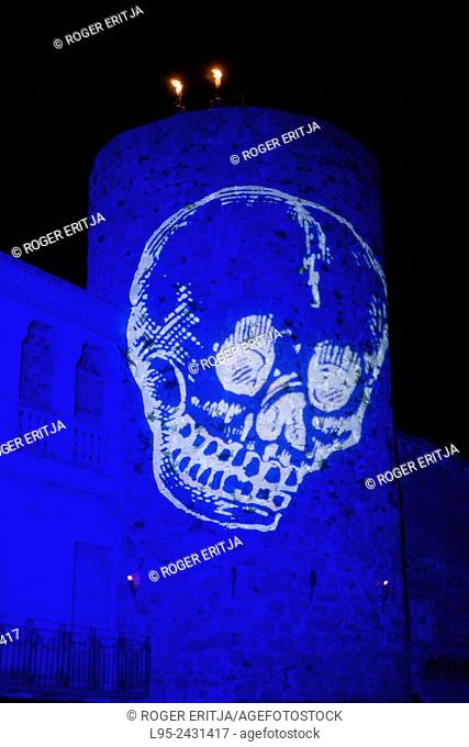 Light projection of a skull over medieval city as part of the feast setup