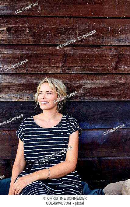 Woman sitting against wooden building