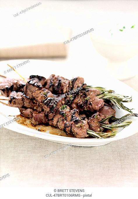 Plate of meat kebabs and herbs