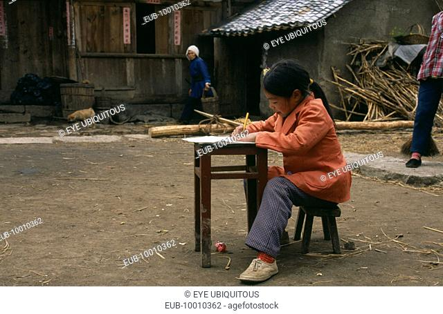 Young girl doing homework at desk in farmyard