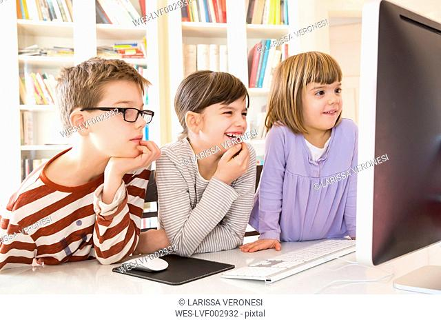 Boy and his two sisters spending time at computer
