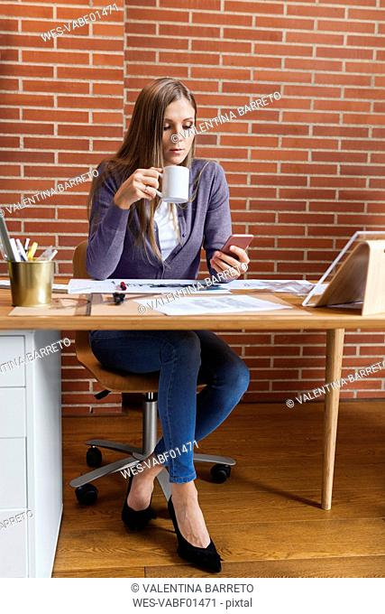 Young woman working in architecture office, using phone