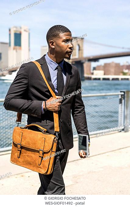 USA, Brooklyn, walking businessman with briefcase and mini tablet