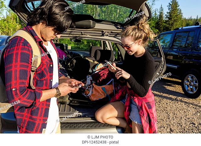 Young couple standing at the back of their packed vehicle with back door open and both using their smart phones; Edmonton, Alberta, Canada