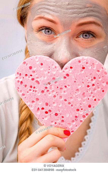 Facial dry skin and body care, complexion treatment at home concept. Happy young woman loving having grey mud mask on her face, holding sponge in heart shape