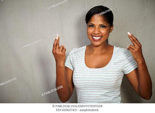 Young african woman in grey blouse crossing her fingers while smiling at the camera