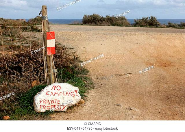 Private Property sign written in red on large white rock