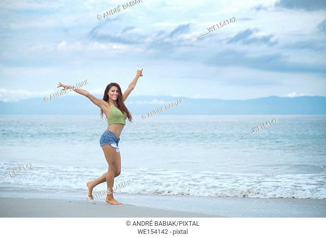 Happy hispanic woman enjoying beach walk