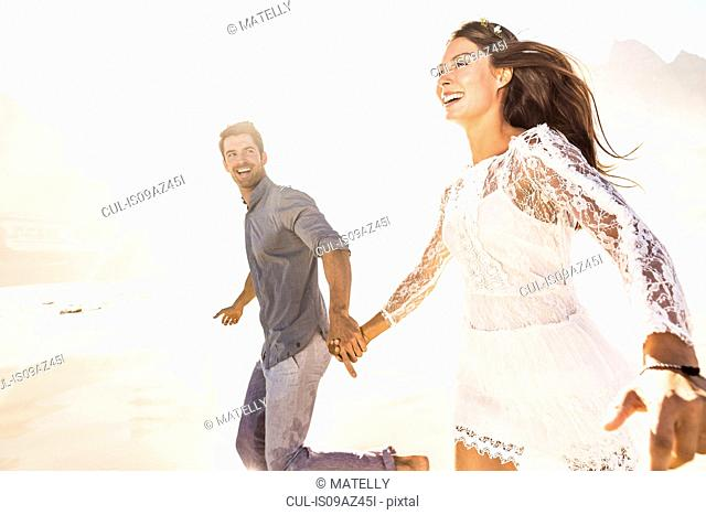 Couple running hand in hand on sunlit beach, Cape Town, South Africa