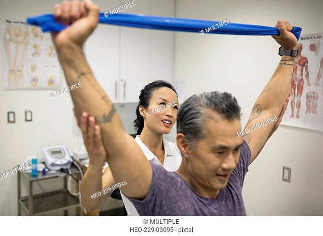 Physical therapist guiding patient pulling resistance band
