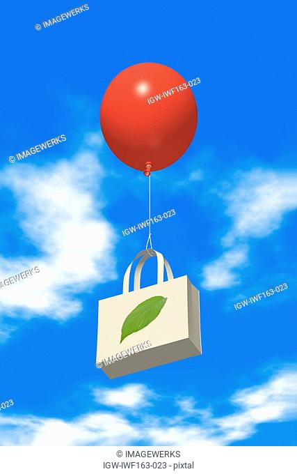 Paper bag tied up with balloon flying in sky