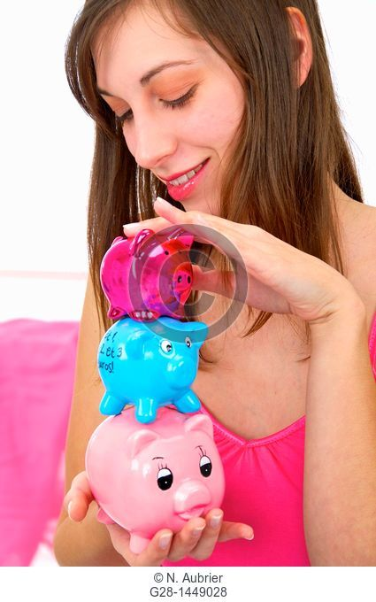 Young woman holding 3 brightly colored piggy money boxes