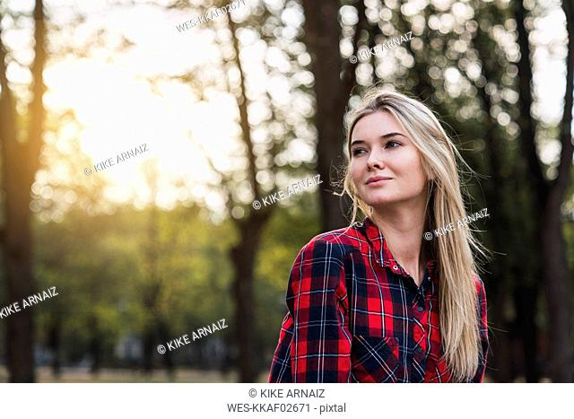 Portrait of young woman wearing plaid shirt in nature