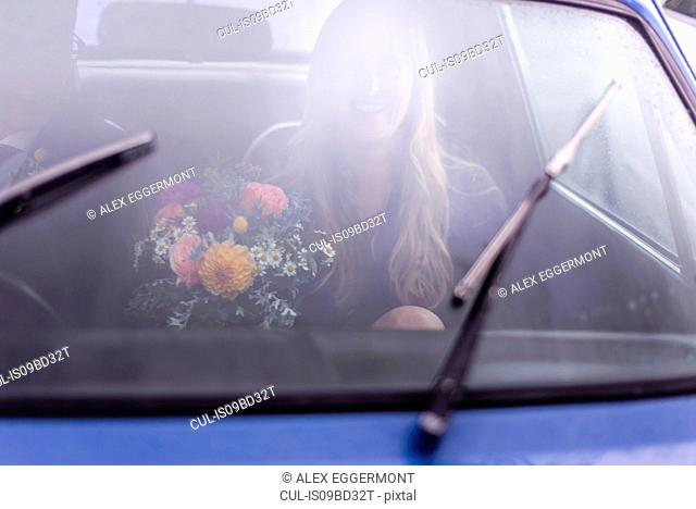 Young woman in car with flower bouquet, driving from wedding