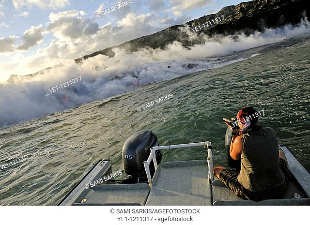 Woman on boat photographing steam rising off lava flowing into ocean, Kilauea Volcano, Hawaii Islands, USA
