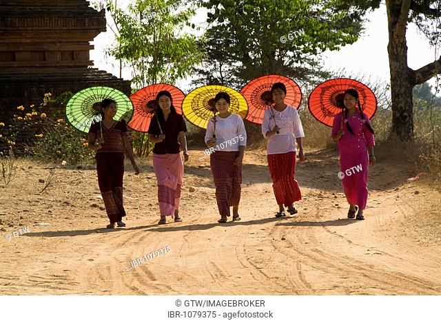 Five young Burmese women walking with coloured parasols, Bagan, Myanmar
