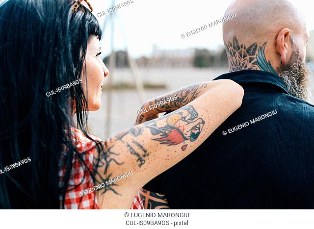 Mature tattooed hipster woman leaning on boyfriends shoulder