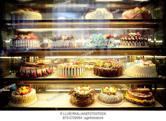 Display of cakes topped with fruits in a Chinese pastry shop. London, England