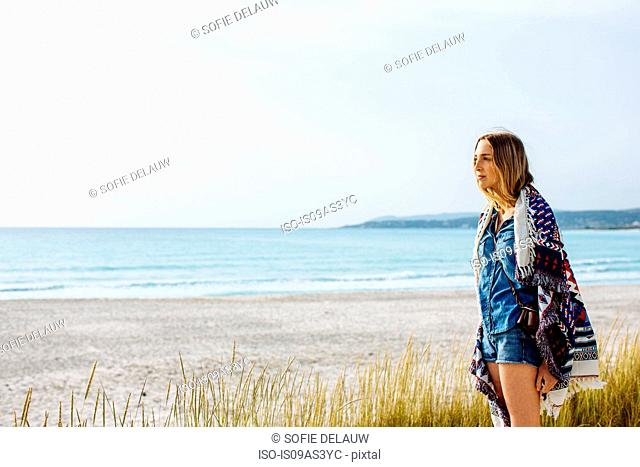 Young woman wrapped in blanket looking out on beach