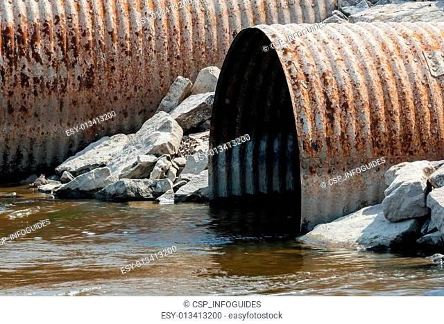 Rusted culvert pipe opening in water