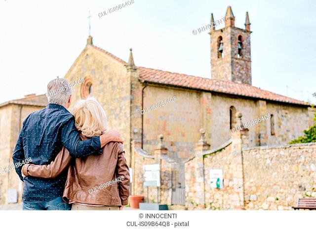 Rear view of tourist couple looking at church, Siena, Tuscany, Italy